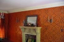 Metallic stencil on orange wall